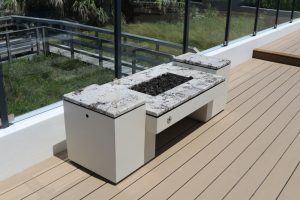 Natural gas powered deck fire pits with decorative glass