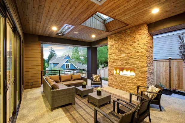 Outdoor covered patio with stone fireplace and furniture.