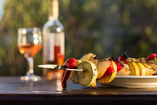 Close up of a table with a veggie kebab and wine glass and bottle.