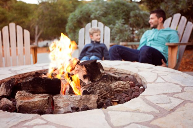 Father and son sitting at a lit, outdoor fireplace.