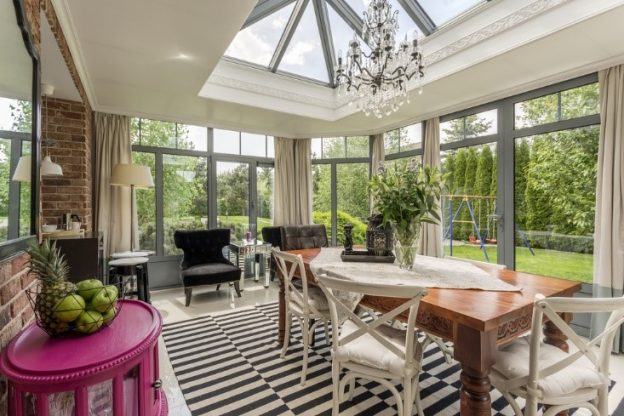 The inside of a sunroom with a table and chairs and a sky light.