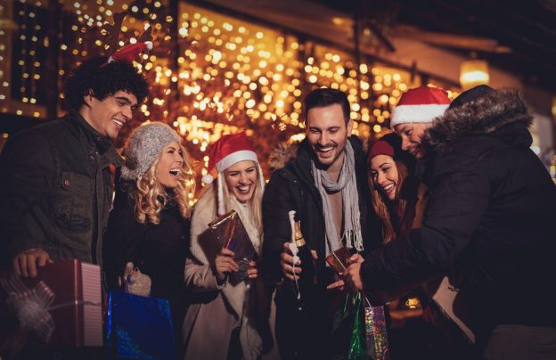 Friends laughing and holding drinks and presents at an outdoor holiday party.