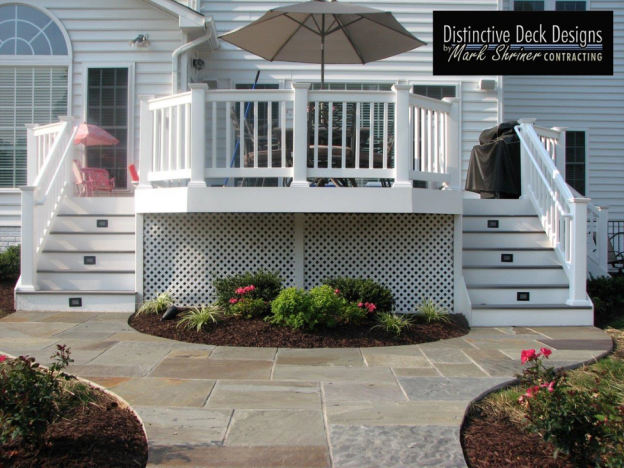 A white, two story deck with stone pavers.