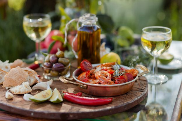 A close-up of a two-person, outdoor dinner with appetizers and wine glasses.