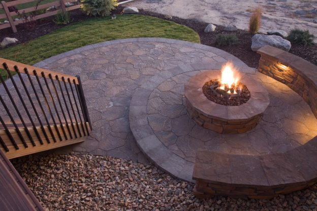 A stone firepit installed in a deck setting.
