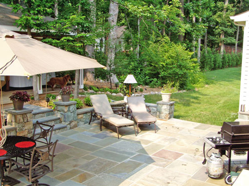 A Virginia backyard with a stone patio and lawn chairs.